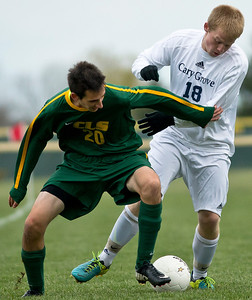 Crystal Lake South's Andrew Perrine fights for the ball with Cary Grove's Danny Kinnerk during the first period of the Regional Semi final match at Crystal Lake South on Wednesday. Crystal Lake South defeated Cary Grove 3-2 in overtime. Brett Moist/ for the Northwest Herald