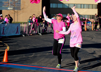 Michelle LaVigne/ For Shaw Media Sue Kies and her 15-year-old daughter cross the finish line on October 18, 2015 in Woodstock,Ill. They ran in honor of Kies sister, Georgianna Kavanagh who died from breast cancer when she was the same age as Faith.