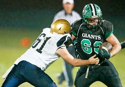 Taylor Glenn (63) from Alden-Hebron is hit at the line by Cole Dunbar (62) from Hiawatha during the second quarter of their game at Alden-Hebron High School on Friday, September 30, 2016 in Hebron, Ill. The Hawks defeated the Green Giants 21-6.  John Konstantaras photo for the Northwest Herald