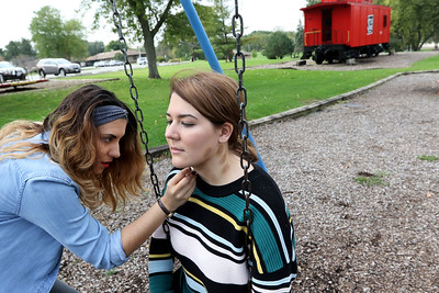 "Candace H. Johnson-For Shaw Media Abbey Bobzin, of Kenosha, Wis., uses makeup to put bruise marks on Jessica Trznadel, of Westchester, before they both act in Scene 13 for the horror movie, ""Tread This Fantasy,"" in the playground at Caboose Park in Lake Villa."