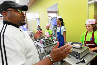 "Candace H. Johnson-For Shaw Media Chef Robert Collins, of North Chicago explains to his students on how to cook a chicken breast on top of the stove to use in salads during ""Salad Day"" at Youthage Culinary Specialist in Mundelein."