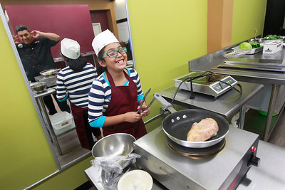 "Candace H. Johnson-For Shaw Media Chef Mario Feijoo, of Wauconda shares a laugh with Candy Rangel, 9, of Mundelein as he instructs her on how to cook a chicken breast in the pan for a chicken caesar salad during ""Salad Day"" at Youthage Culinary Specialist in Mundelein."