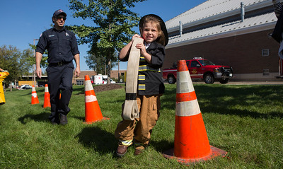 Mike Greene - For Shaw Media  Elizha Poierier, 4 of McHenry, carries a hose through the obstacle course during the Crystal Lake Fire Rescue Open House Saturday, October 8, 2016 in Crystal Lake. The annual event featured station tours, fire extinguisher demos, hands only CPR, Flight for Life helicopter tours as well as gear demos, sonar rescue and dive rescue demos, and kid's obstacle courses.
