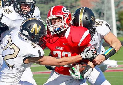 Candace H. Johnson-For Shaw Media Grant's Isaac Jaime gets tackled by Grayslake North's Giananthony Ocampo and Charles Burr in the second half at Grant Community High School in Fox Lake.