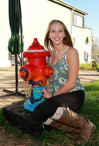 """Candace H. Johnson-For Shaw Media Kristina Bell, 16, of Fox Lake sits by her fire hydrant called, """"Anchor"""", next to the Village Bakery on Grand Avenue in Fox Lake."""