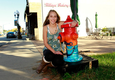 """Candace H. Johnson-For Shaw Media Kristina Bell, 16, of Fox Lake sits by her fire hydrant called, """"Anchor,"""" next to the Village Bakery & Cafe on Grand Avenue in Fox Lake."""