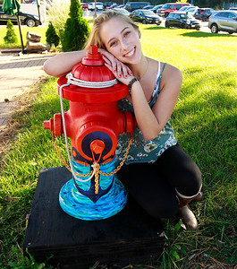 "Candace H. Johnson-For Shaw Media Kristina Bell, 16, of Fox Lake sits by her fire hydrant called, ""Anchor,"" outside the Village Bakery & Cafe on Grand Avenue in Fox Lake."