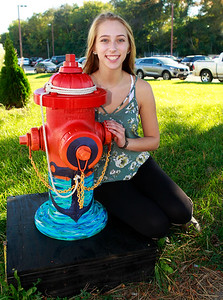 """Candace H. Johnson-For Shaw Media Kristina Bell, 16, of Fox Lake sits by her fire hydrant called, """"Anchor"""", near the Village Bakery & Cafe on Grand Avenue in Fox Lake."""