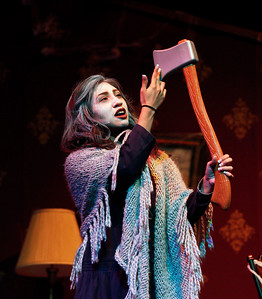 "The Woman, senior Karla Juarez, looks at her axe during the rehearsal for the play ""Honeymoon at Graveside Manor"" at Marian Central Catholic on Tuesday, October 18, 2016 in Woodstock, Ill. John Konstantaras photo for the Northwest Herald"