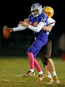 Jacob Vincent (12) from Hampshire is called for intentional grounding as he is sacked by Eric Schutt (72) from Jacobs during the third quarter of their game at Hampshire High School on Friday, October 21, 2016 in Hampshire.  John Konstantaras photo for the Northwest Herald