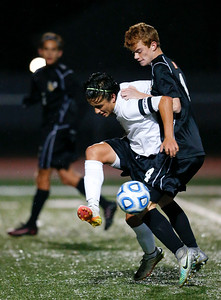 Ian Tapia (left) from McHenry holds back Patrick Murphy (4) from Jacobs as the battle for a ball during the first half of their Class 3A Huntley Boys Soccer Sectional semi-final on Tuesday October 25, 2016 in Huntley. The Golden Eagles defeated the Warriors 2-1.  John Konstantaras photo for the Northwest Herald
