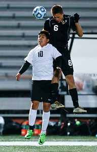 Noah Melick (6) from Jacobs heads the ball over Charlie Mendez (10) from McHenry during the first half of their Class 3A Huntley Boys Soccer Sectional semi-final on Tuesday October 25, 2016 in Huntley. The Golden Eagles defeated the Warriors 2-1.  John Konstantaras photo for the Northwest Herald