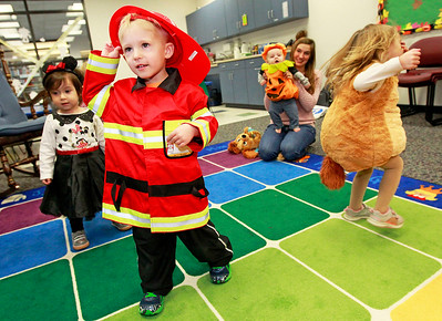Candace H. Johnson-For Shaw Media Victoria Castillo, 2, of Antioch, Owen Sternberg, 3, of Trevor, Wis. and Audrey Sparrowgrove, 2, of Spring Grove dance to the music during the Tiny Tots Halloween program at the Antioch Public Library District.