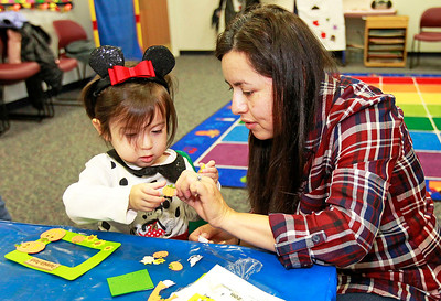 Candace H. Johnson-For Shaw Media Victoria Castillo, 2, of Antioch and her mother, Galia, make a Pumpkin Patch picture frame during the Tiny Tots Halloween program at the Antioch Public Library District.