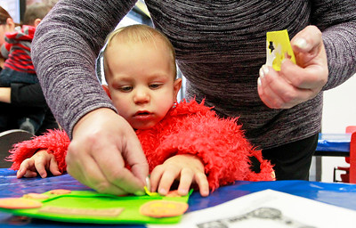 Candace H. Johnson-For Shaw Media Levi Pauley, fifteen-months-old, of Trevor, Wis., dressed as Elmo and his grandmother, Rita Chernin, of Grayslake make a frame craft during the Tiny Tots Halloween program at the Antioch Public Library District.