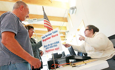 Candace H. Johnson-For Shaw Media Ron and Stacey Bing, of Lake Villa register to vote with Charisse Bruno, of Buffalo Grove, election judge, during Early Voting at the Antioch Township Hall in Lake Villa.