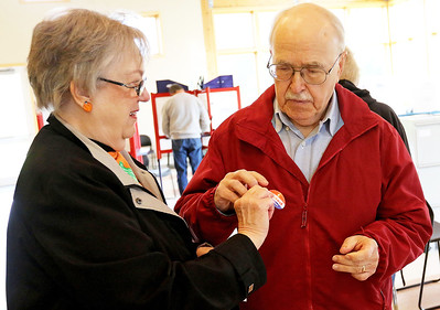"Candace H. Johnson-For Shaw Media Yvonne Meltzer, of Antioch hands her husband, Paul, his ""I Voted Today!"" sticker after they voted during Early Voting at the Antioch Township Hall in Lake Villa."