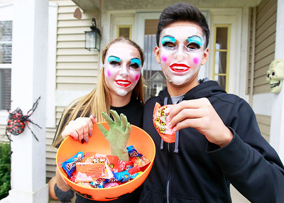 Candace H. Johnson-For Shaw Media Eliza Scoggin and Brian Dorantes, 14, both of Round Lake hand out candy during trick-or-treating in the Valley Lakes subdivision in Round Lake.
