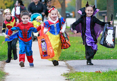 Candace H. Johnson-For Shaw Media Hailey Downing, 7, of McHenry, Lucas Madro, 3, Jadyn Ozick, 5, and Leah Madro, 7, all of Ingleside run house-to-house trick-or-treating down a street in Ingleside.