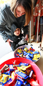 Candace H. Johnson-For Shaw Media Enzo Ramirez, 2, of Round Lake Park gets some help from his mother, Rebecca, picking out candy as they trick-or-treat in the Valley Lakes subdivision in Round Lake.