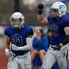 St. Charles North's Brenden Norbert (21) and Christopher Cotter (55) celebrate a touchdown against Carmel on Oct. 29 at the Class7A playoff game in St. Charles.