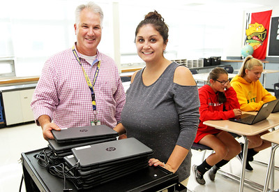 Candace H. Johnson-For Shaw Media Eighth grade teachers Michael Dean and Stephanie Kaye stand next to the HP ProBook x360 Notebook PC laptops  they bought for their students after having raised the money from private donations and a GoFundMe campaign at Gavin South Middle School in Ingleside.