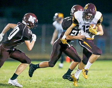 Anthony Rivera (12) from Richmond-Burton is tackled by Michael Anderson (21) from Marengo after making a first down catch during the second quarter of their game at Marengo High School on Friday, October 6, 2017 in Marengo, Illinois. John Konstantaras photo for Shaw Media