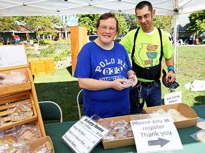 Candace H. Johnson-For Shaw Media Residents Nicki Gras and Andy Wernick show what baked goods are for sale from the Sugar Maple Country Store during Fall on the Farm & Community Tent Sale at Lambs Farm in Libertyville. The baked goods were made at Lambs Farm.