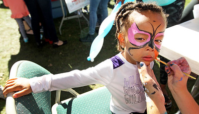 Candace H. Johnson-For Shaw Media Skylar Cabichon, 3, of Beverly gets a butterfly painted on her face by Iviiy Salavar, 16, of Mundelein during Fall on the Farm & Community Tent Sale at Lambs Farm in Libertyville.