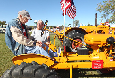 Candace H. Johnson-For Shaw Media Resident Marc Nachtman talks with Chuck Hartman, of Des Plaines, with the Lake County Farm Heritage Association, about the 1952 Minneapolis Moline tractor he was sitting on during Fall on the Farm at Lambs Farm in Libertyville.