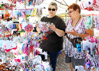 Candace H. Johnson-For Shaw Media Christine Franklin, of Round Lake talks to Carole Genovese, of River Grove, with Carole's Boutique, about the hair bows she was selling in her booth during Fall on the Farm & Community Tent Sale at Lambs Farm in Libertyville.