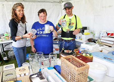 Candace H. Johnson-For Shaw Media Kathy McMeins, special events coordinator, stands next to Nicki Gras and Andy Wernick, residents, as they look at drinking glasses in the Community Tent Sale during Fall on the Farm at Lambs Farm in Libertyville. The items came from the Cedar Chest Thrift Shop which has donated items for sale on the property.