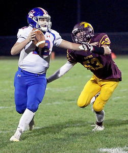 Candace H. Johnson-For Shaw Media Genoa-Kingston's quarterback, Griffin Hansen, looks to make a pass against Richmond-Burton's Dom Rivas in the second quarter at Richmond-Burton High School.