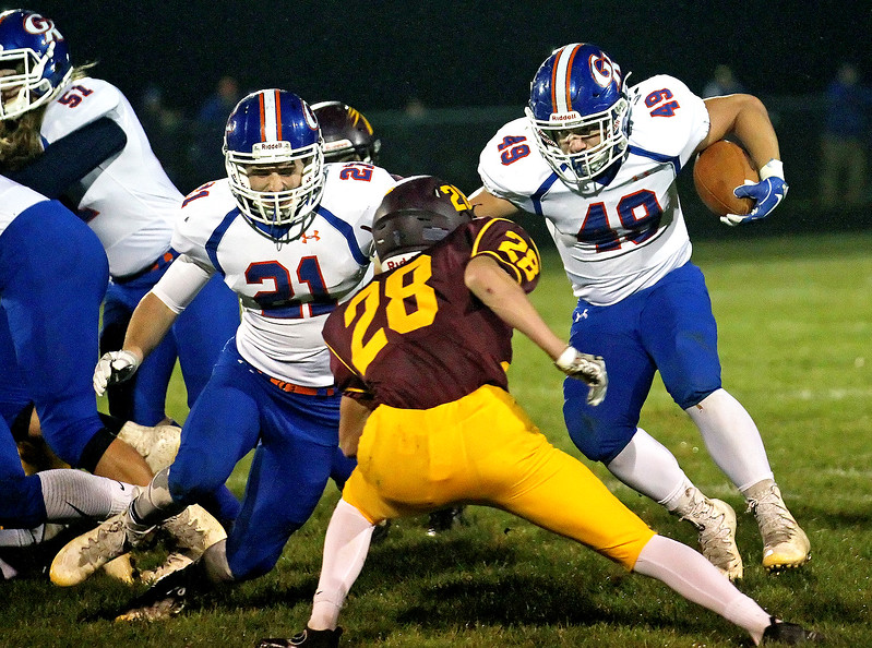 Candace H. Johnson-For Shaw Media Genoa-Kingston's Jackson Ebel (#49) looks to get around the tackle attempt by Richmond-Burton's Payton Minzey in the first quarter at Richmond-Burton High School.