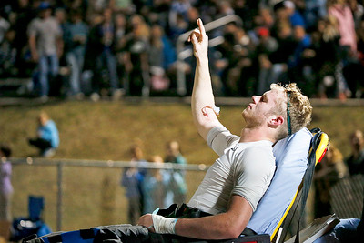 Quarterback Collin Mergl (10) from Woodstock North raises his arm as he is moved to an ambulance after being injured on his touchdown run during the first quarter at Woodstock High School on Friday, October 13, 2017 in Woodstock, Illinois. John Konstantaras photo for Shaw Media