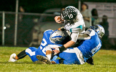Collin Mergl (10) from Woodstock North is tackled in the end zone by David Shinherr (20, left) and Michael Gardner (8) from Woodstock during the first quarter at Woodstock High School on Friday, October 13, 2017 in Woodstock, Illinois. Mergl was injured on the play. John Konstantaras photo for Shaw Media