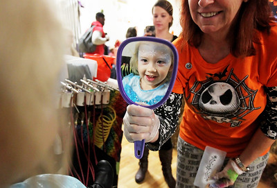 Candace H. Johnson-For Shaw Media Kylie Carter, 3, of Antioch looks at herself in the mirror after getting her face painted by Kat Beringer with Head 2 Toe Bodyart during the Haunted Trail at the Lindenhurst Park District's Community Center on Grass Lake Road.