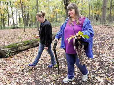 Candace H. Johnson-For Shaw Media Ashley Carey and her mother, Denise, both of Round Lake go on a nature hike through Hart's Woods during the Oaktober Celebration at the Round Lake Area Park District's Aquatic Center and Nature Museum in Round Lake. Denise Carey found a walking stick in the woods and left it behind  for the next person.