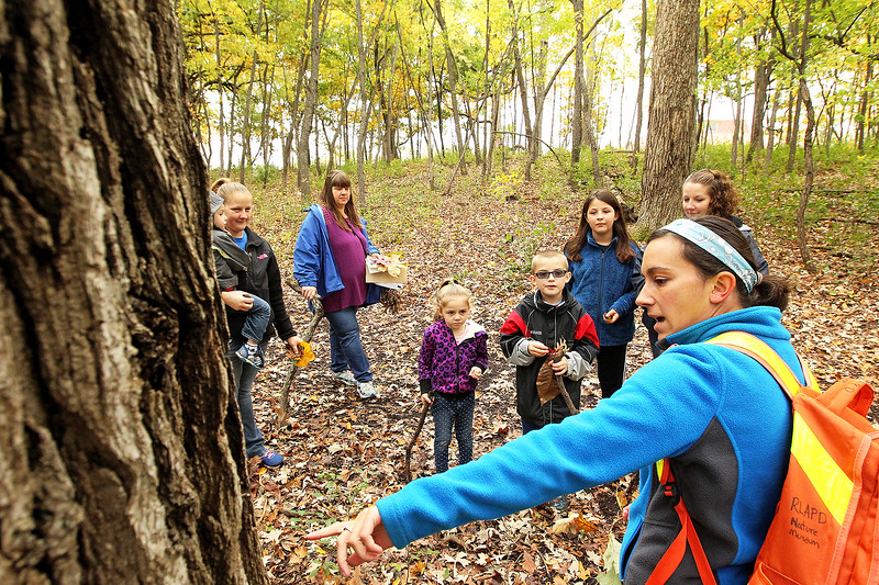 Candace H. Johnson-For Shaw Media Christine Kustra, recreation supervisor, takes a group on a nature hike through Hart's Woods and points out a burr oak tree during the Oaktober Celebration at the Round Lake Area Park District's Aquatic Center and Nature Museum in Round Lake.