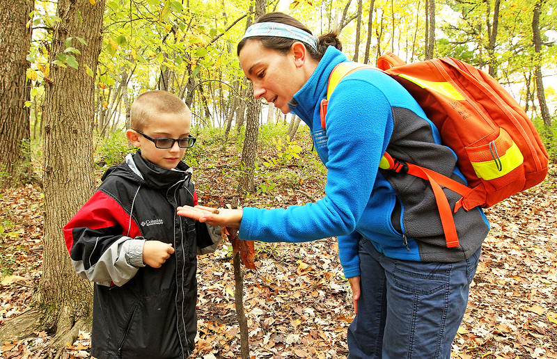 Candace H. Johnson-For Shaw Media Logan Carey, 7, of Round Lake talks to Christine Kustra, recreation supervisor, about the white acorn she is holding that they found on their nature hike through Hart's Woods during the Oaktober Celebration at the Round Lake Area Park District's Aquatic Center and Nature Museum in Round Lake.
