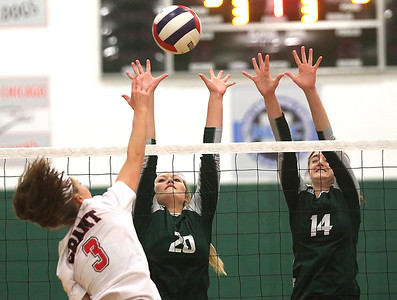 Candace H. Johnson-For Shaw Media Grant's Megan Mitchell gets past the block of Grayslake Central's Lauren LaBeck and Kate Bullman in the first set at Grayslake Central High School. Grant won, (25-22, 26-28, 25-23)