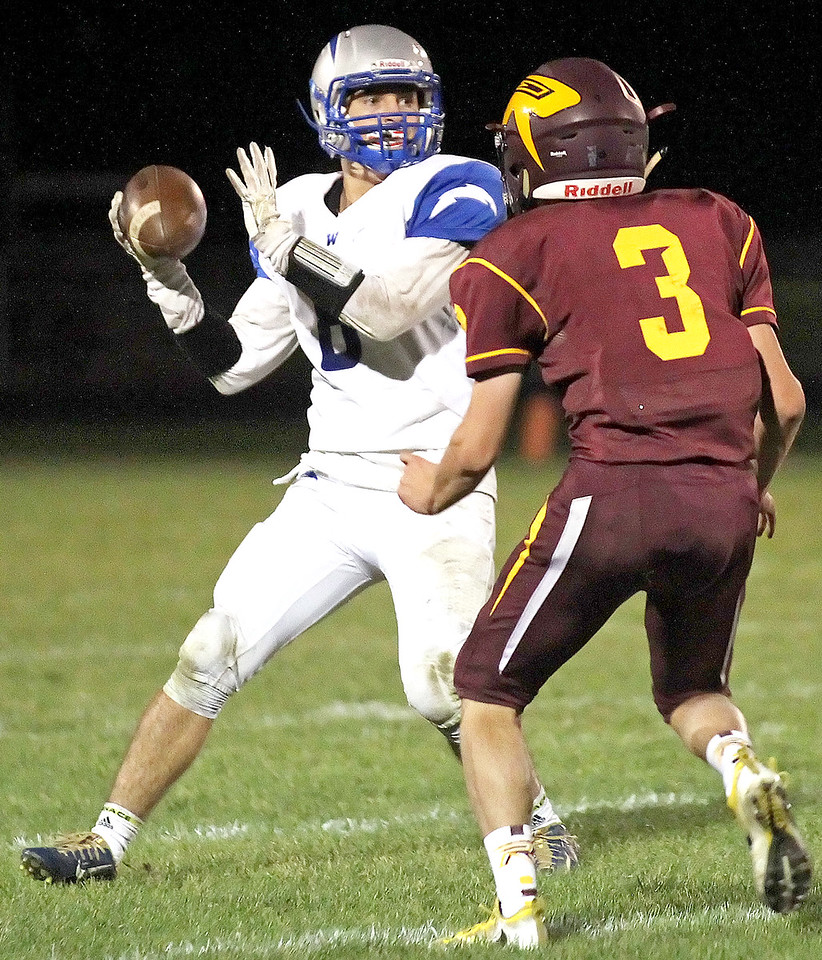 Candace H. Johnson-For Shaw Media Woodstock's Michael Gardner looks to pass against Richmond-Burton's Benjamin Orkild in the second quarter at Richmond-Burton High School.