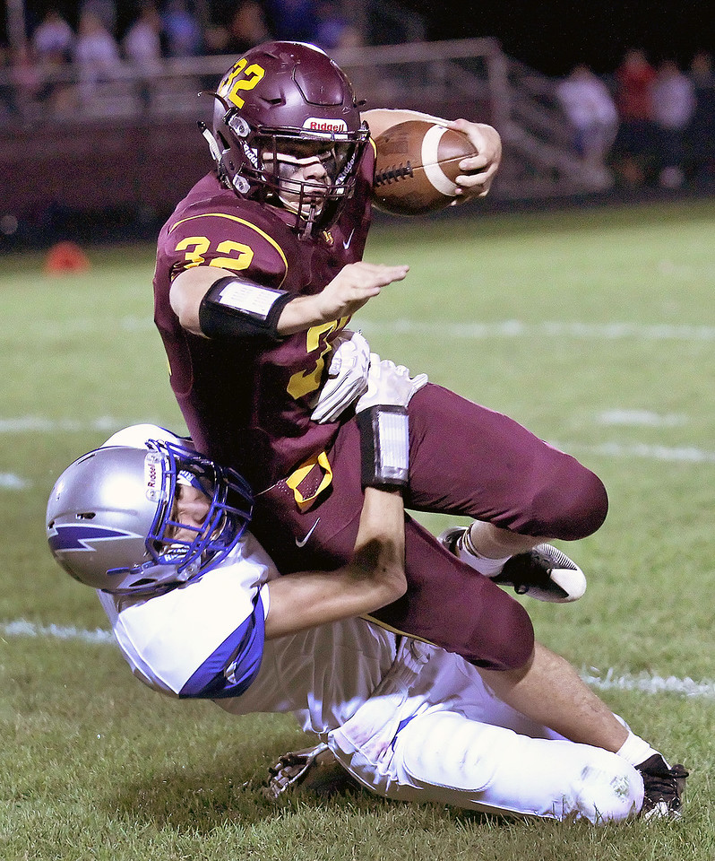 Candace H. Johnson-For Shaw Media Richmond-Burton's James Harner is tackled by a Woodstock's Dane Clute in the first quarter at Richmond-Burton High School.