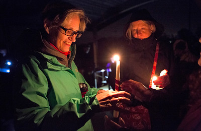 Mike Greene - For Shaw Media  Marybeth Urbin, left, of Woodstock, and Cathy Johnson, of Marengo, help others with their candles during a prayer vigil held in support of immigrants detained in the McHenry County Jail and threatened Dreamers Sunday, October 22, 2017 at Bates Park in Woodstock. The event featured multiple speakers, prayers, and songs culminating in a candlelit walk to the McHenry County Jail.