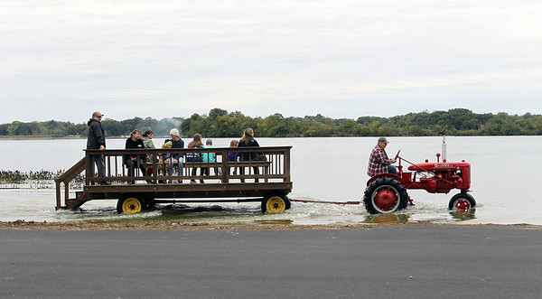 Candace H. Johnson-For Shaw Media Ron Thompson, of Lake Zurich drives his 1946 Farmall B tractor through the shallow end of Cedar Lake as he gives a hayride to a group of visitors during the Busy Brains Children's Museum Fall Family Festival at Lehmann Park in Lake Villa. (9/29/18)