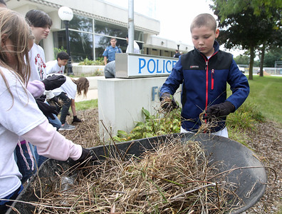 Candace H. Johnson-For Shaw Media Stanton Middle School's Nathan Sosnowski, 11, of Fox Lake (on right) pulls weeds in front of the Fox Lake Police Dept. on Route 59 during the Fox Lake Grade School District 114's 4th Annual Day of Service. (9/28/18)