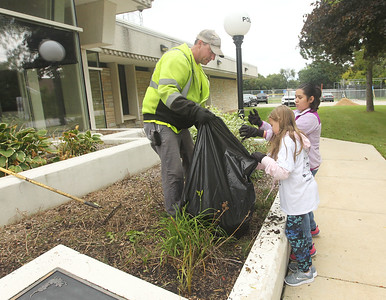 Candace H. Johnson-For Shaw Media Mike Sprague, maintenance worker with the Fox Lake Street Dept., gets help from Hailey Montanez and Rosely Castaneda, both 11, of Fox Lake pulling weeds outside of the Fox Lake Police Dept. on Route 59 during the Fox Lake Grade School District 114's 4th Annual Day of Service. (9/28/18)