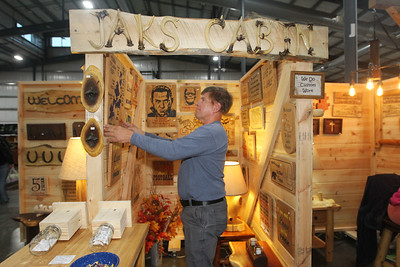 Candace H. Johnson-For Shaw Media Jeff Dee, of Lindenhurst with Jaks Cabin adjusts one of his rustic decor wood carvings in his booth during the Art & Craft Show at the Lake County Fairgrounds in Grayslake. The event was hosted by Step By Step Promotions. The next craft show will be held at the Lake County Fairgrounds on Thanksgiving weekend, Friday through Sunday, November 23rd-25th.(10/7/18)