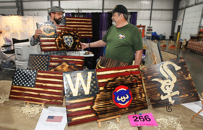 Candace H. Johnson-For Shaw Media Eric Shrum, of Johnsburg with The Burning Man Eric Shrum shows his father, Jim Shrum, of McHenry one of his handmade wooden American flags he was selling during the Art & Craft Show at the Lake County Fairgrounds in Grayslake. Eric's father, Jim, is a Vietnam veteran. The event was hosted by Step By Step Promotions. The next craft show will be held at the Lake County Fairgrounds on Thanksgiving weekend, Friday through Sunday, November 23rd-25th.(10/7/18)