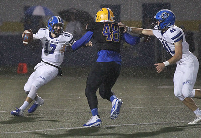 Candace H. Johnson-For Shaw Media Lake Zurich's Matt McGraw looks to pass with help from Jack Dwyer against Warren's Malachi McNeal (#48) in the second quarter on a rainy night at Warren Township High School in Gurnee. Warren won 34-6. (10/5/18)
